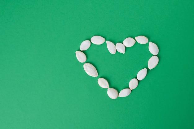 Forme de coeur faite de graines de citrouille sur fond vert.