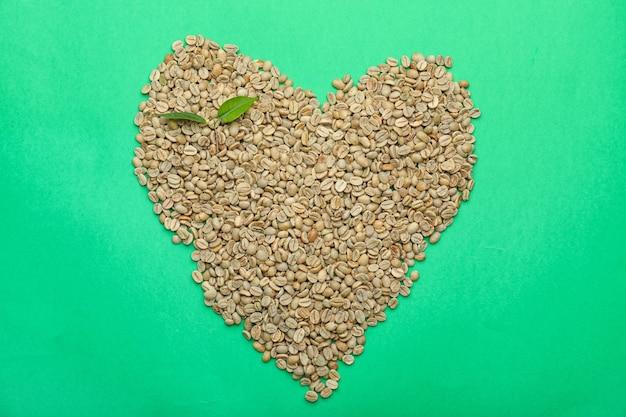 Forme de coeur faite de grains de café verts sur la couleur