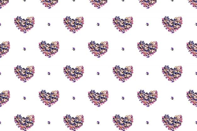 Forme de coeur faite de pétales de fleurs sur blanc