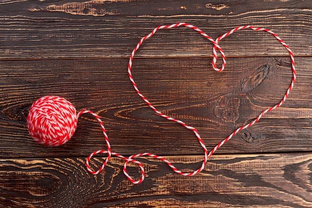 Forme de coeur en fil de laine. boule de laine sur fond en bois marron.