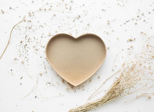 Forme de coeur avec fleur de branche sèche et sur fond blanc