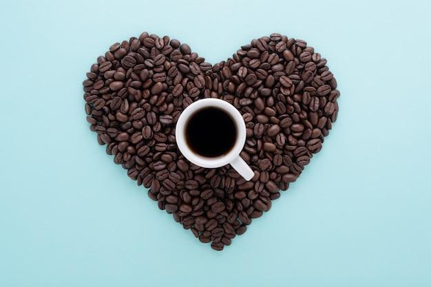 Forme de coeur de grains de café et tasse de café sur bleu.