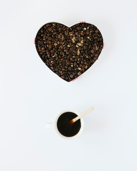 En forme de coeur avec des grains de café et une tasse à café
