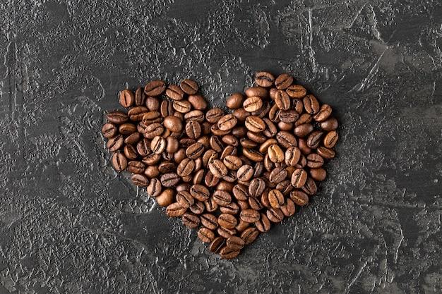 En forme de cœur de grains de café torréfiés sur fond sombre