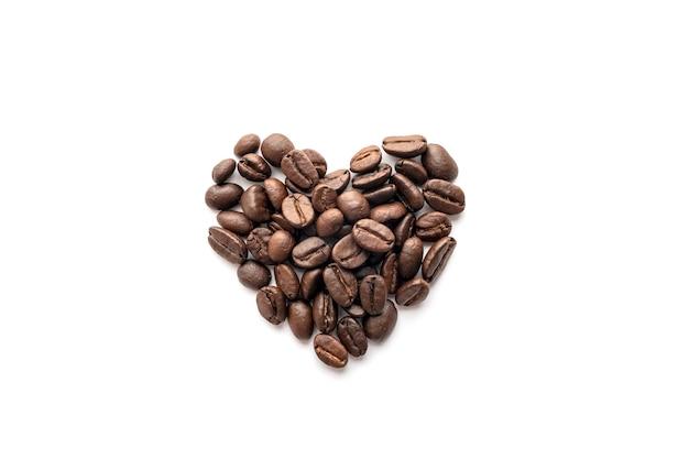 En forme de cœur de grains de café torréfiés isolés sur fond blanc.