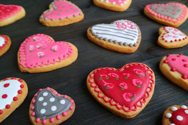 En forme de coeur avec de jolis cookies de glaçage royal sur fond de bois noir