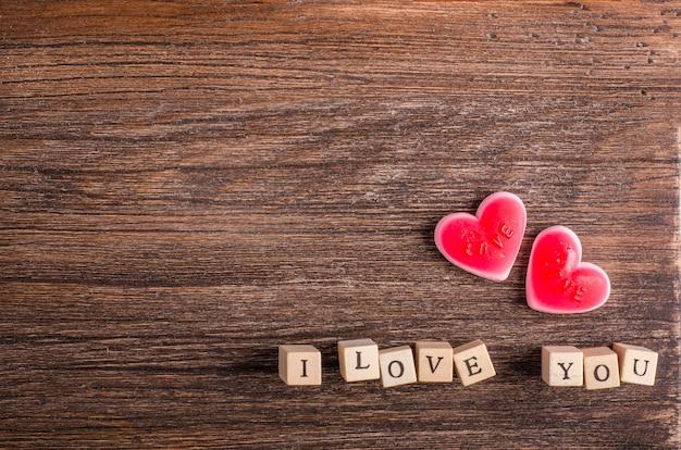 En forme de coeur mâchant des bonbons et des mots je t'aime sur des cubes, fond en bois.