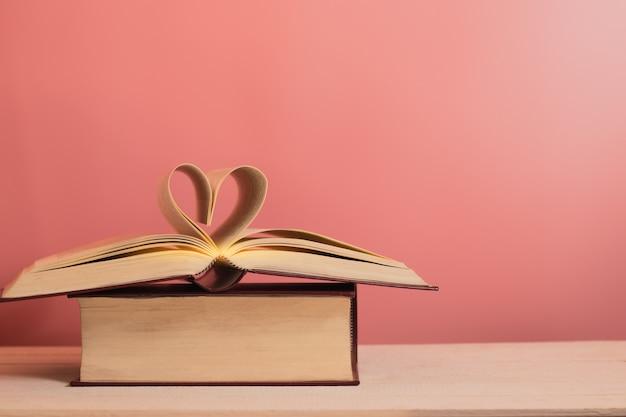 Forme de coeur des pages du livre sur le plancher en bois pour le fond.