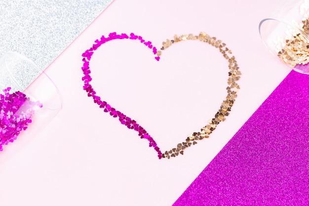Forme de coeur en paillettes multicolores. deux verres de champagne avec des éclaboussures de confettis en forme de coeur sur fond de paillettes