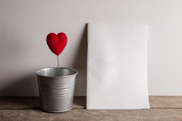 La forme de coeur sur le pot de zinc et livre blanc pour votre message