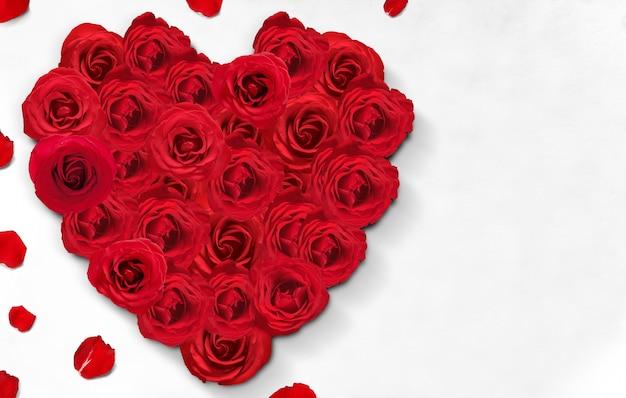 La forme de coeur de roses rouges et de pétales de rose sur le sol