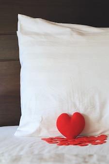 Forme de coeur rouge sur le lit et contre l'oreiller