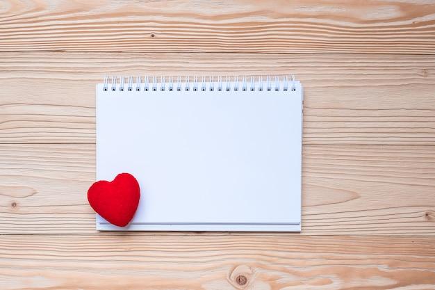 Forme de coeur rouge avec ordinateur portable sur fond de table en bois.