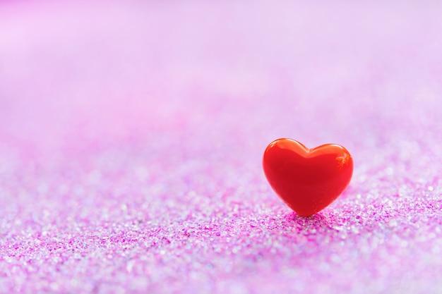 Forme de coeur rouge sur une surface abstraite de paillettes rose clair