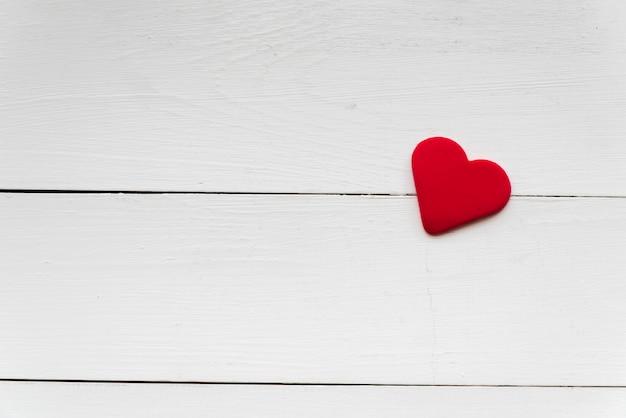 Forme de coeur rouge tendre sur une planche en bois blanche