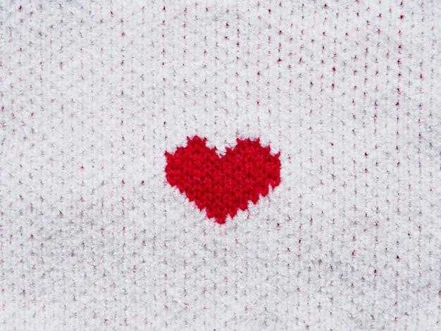 Forme de coeur rouge sur la texture du tissu blanc. fond de concept de la saint-valentin.