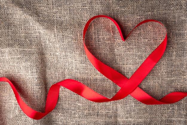 Forme de coeur de ruban rouge sur toile de lin