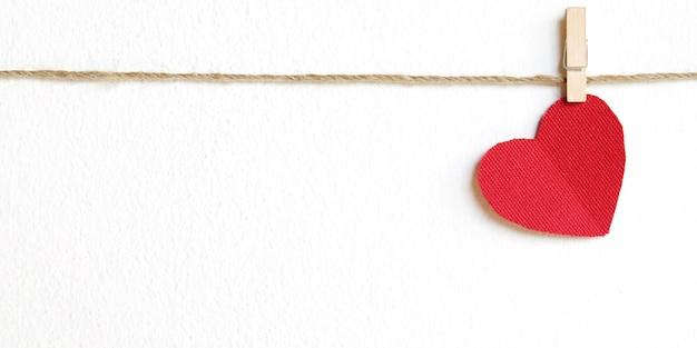 Forme de coeur de tissu rouge accroché sur backgroun blanc