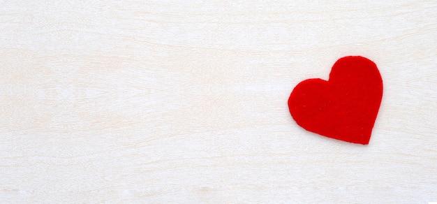 Forme de coeur de tissu rouge sur fond de bois blanc. fond de la saint-valentin.