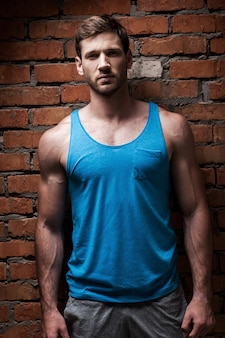 En forme et confiant. confiant jeune homme musclé posant debout contre le mur de briques
