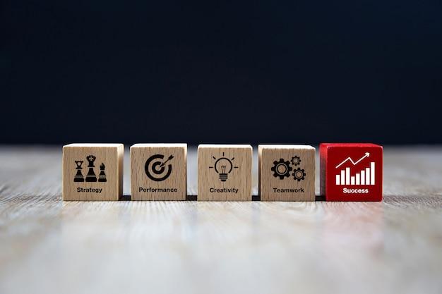 Forme de cube en bois avec des icônes de l'entreprise.