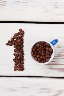 Forme de grain numéro un et tasse de café. vue de dessus. planches de bois blanches en surface.