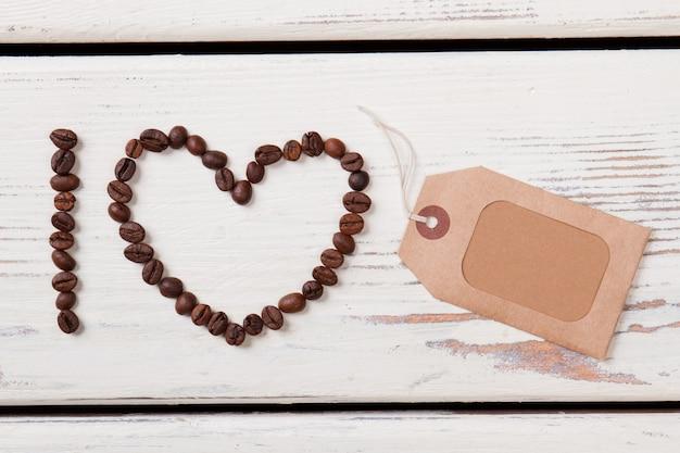 Forme de grains de café et étiquette d'étiquette en papier. planches de bois blanches. mise à plat.