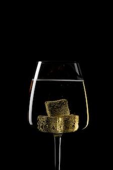 Forme de gros plan de verre avec des glaçons dans l'obscurité
