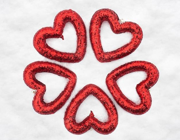 Forme de jouets coeur rouge sur fond de neige
