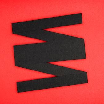 Forme linéaire géométrique abstraite noire sur fond rouge