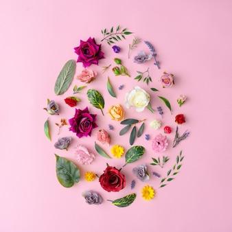 Forme d'oeuf de pâques faite avec diverses fleurs printanières et feuilles sur rose pastel. concept minimal de joyeuses pâques.
