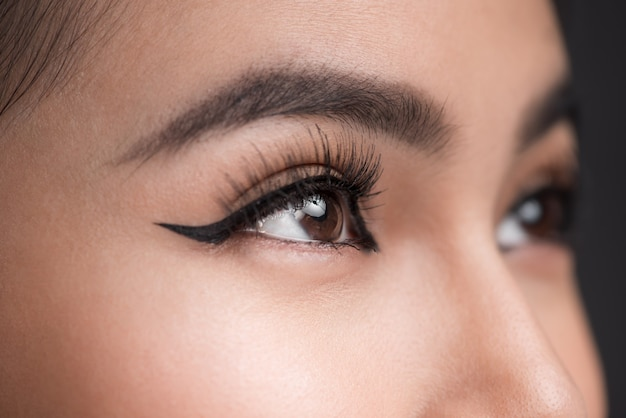 Forme parfaite des sourcils. belle photo macro d'un œil féminin avec un maquillage eye-liner classique.