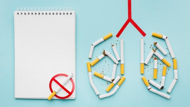 Forme des poumons avec des cigarettes et un cahier à côté