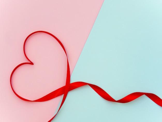 Forme de ruban coeur sur fond pastel rose et cyan avec espace de copie pour la saint-valentin.