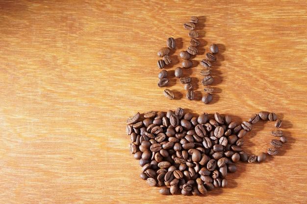 Forme de tasse à café de grains de café torréfiés sur fond en bois