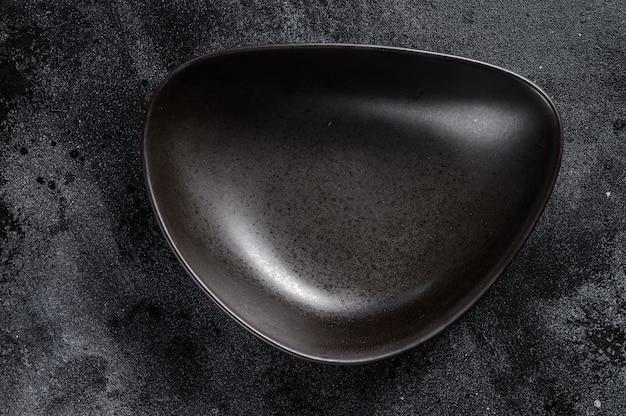 Forme triangulaire de plaque noire sur fond noir texturé