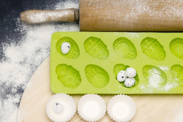 Forme verte en silicone pour la cuisson de petits gâteaux de pâques sur fond noir avec de la farine