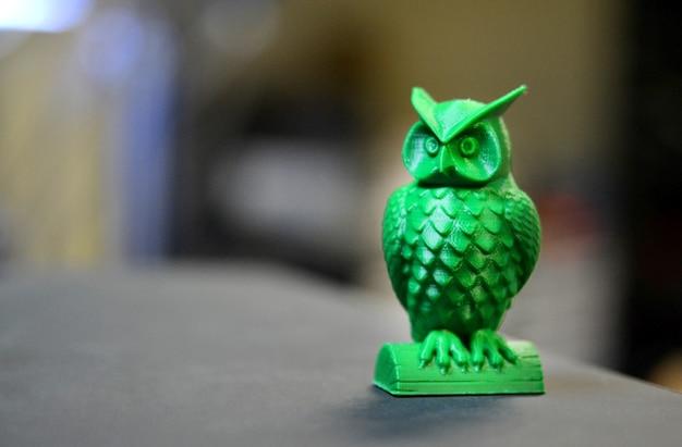 La forme verte sous la forme d'un petit hibou créé sur fond sombre de l'imprimante 3d