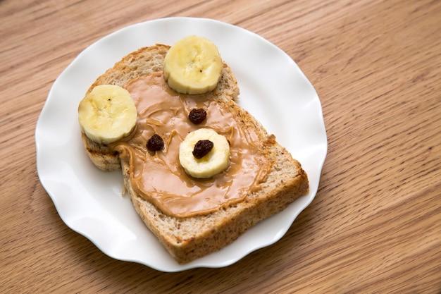 Forme de visage d'ours pain de blé entier avec beurre d'arachide, banane et raisin sec
