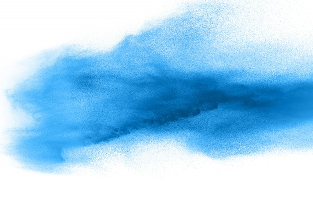 Des formes bizarres de poudre bleue explosent en nuage sur fond blanc.