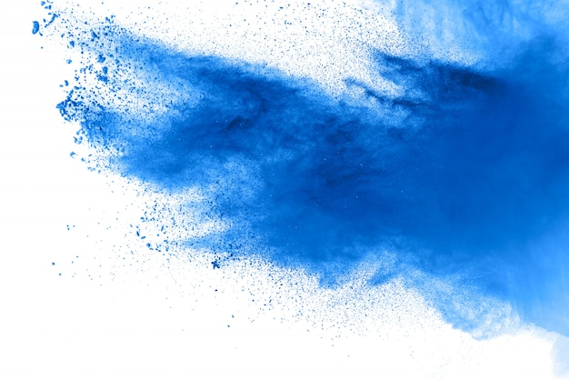 Des formes bizarres de poudre bleue explosent en nuage sur le fond. lancé des particules de poussière bleue sp
