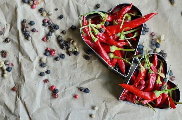 Formes de coeur en aluminium remplis de petits piments chili sur fond de papier vintage