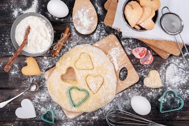 Formes de coeur saint valentin en pâte avec des ustensiles de cuisine