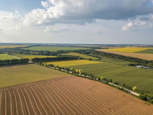 Formes géométriques abstraites de champs agricoles avec différentes cultures et sols sans semis de cultures, séparés par une route avec une rivière, des arbres aux couleurs jaune vert. une vue plongeante depuis le drone.