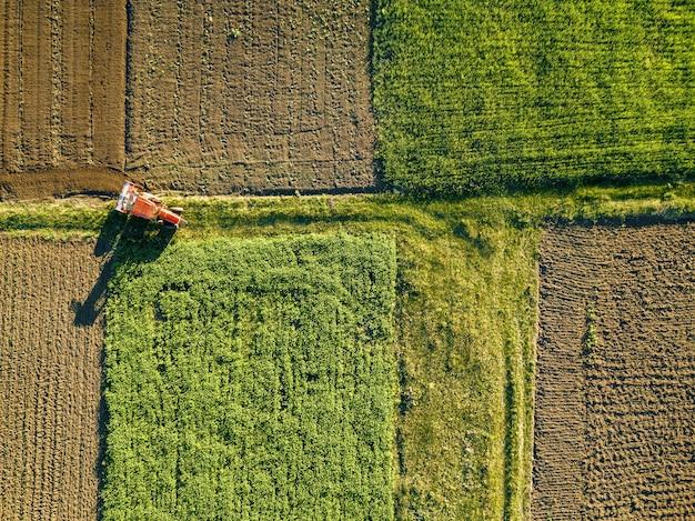 Formes géométriques abstraites de champs agricoles avec différentes cultures et sols sans semis de cultures, séparés par une route et un tracteur, dans des couleurs vertes et noires. une vue plongeante depuis le drone.