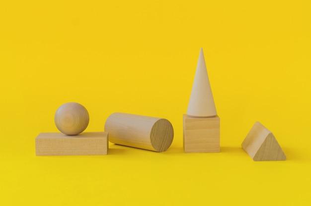 Formes géométriques en bois sur fond jaune. apprentissage préscolaire.