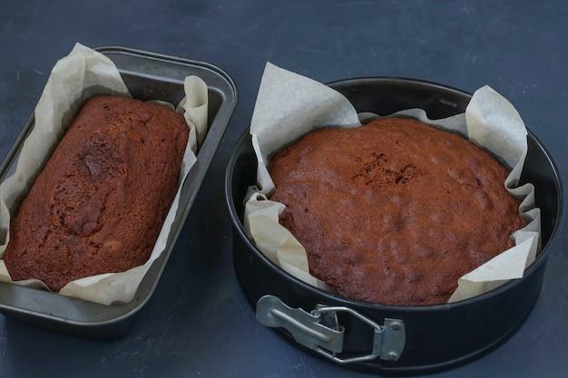 Des formes rondes et rectangulaires sont posées avec du papier parchemin avec un biscuit prêt pour le gâteau pancho sur fond sombre, orientation horizontale