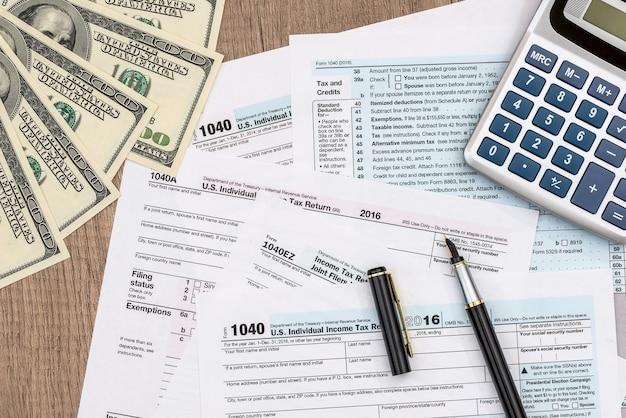 Formulaire 1040 avec dollar, stylo et calculatrice