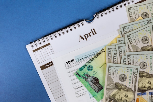 Formulaire de déclaration de revenus irs 1040 avec la devise des billets en dollars américains de relance de la déclaration de revenus économiques chèque close up