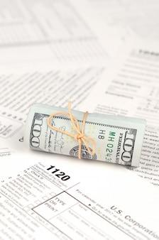 Formulaire de déclaration de revenus des sociétés américaines 1120 avec rouleau de billets en dollars américains